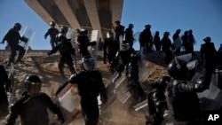 Polisi Meksiko berlari ketika mereka mencoba untuk mencegah migran melewati perbatasan Chaparral di Tijuana, Meksiko, dekat San Ysidro, California, Minggu, 25 November 2018.