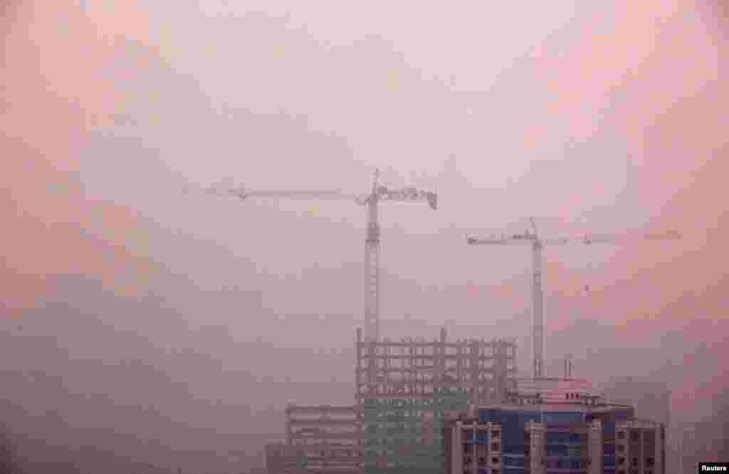 Cranes atop a residential building under construction in central Beijing, April 18, 2012.