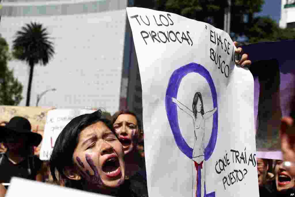 """En México, unas 200 personas se concentraron en la estatua del Ángel de la Independencia con carteles con leyendas como """"Ni una más"""" mientras gritaban """"¡Aunque traiga escote, aunque traiga falda, no quiero ser asesinada!""""."""
