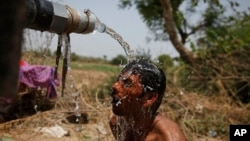 An Indian man takes bath under the tap of a water tanker on a hot day in Ahmadabad, India, May 21, 2015.