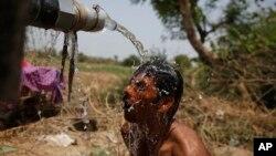 Un indien s'asperge de l'eau sous un robinet suite à des chaleurs élevées à Ahmadabad, Inde, jeudi 21 mai 2015.