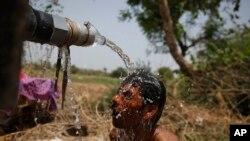 Một người đàn ông tắm dưới vòi của một xe chở nước tại Ahmadabad, Ấn Độ.
