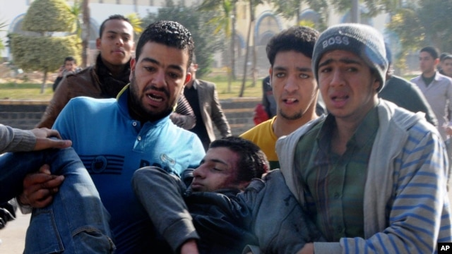 Egyptian men try to help save the life of an al-Azhar University student heavily injured from clashes outside the university in Cairo, Egypt, Sunday, Dec. 29, 2013.