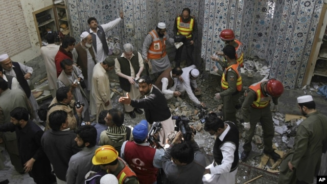 Pakistani security officials and rescue workers examine the site of bomb blast inside a mosque in Peshawar, Pakistan, March 09, 2013.