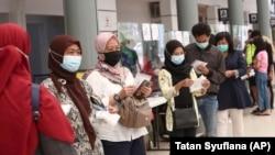 Para calon penumpang antre untuk tes virus corona untuk perjalanan kereta jarak jauh di Stasiun Pasar Senen, Jakarta, 9 Februari 2021. (Foto: Tatan Syuflana/AP)