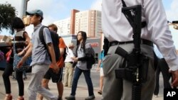 Andrew Clements, right, a licensed gun owner, open carrying a high-velocity rifle, demonstrates on Guadalupe St., next to the University of Texas, in Austin, Texas, Aug. 24, 2016.