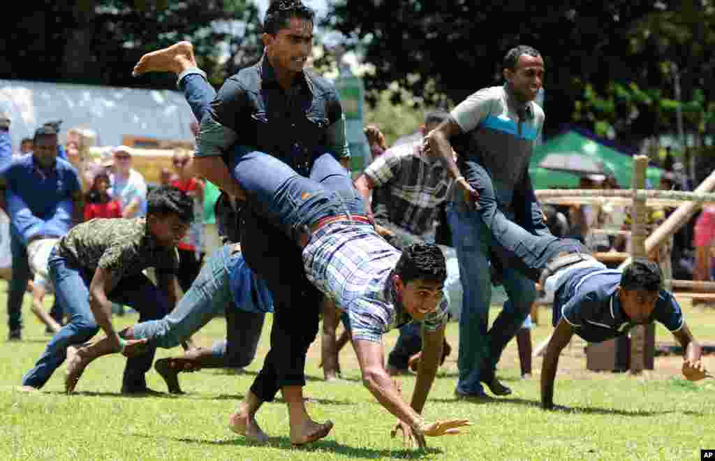 People participate in a traditional game during Sinhala and Tamil New Year celebrations in Colombo, Sri Lanka.  Sinhalese and Tamil communities will mark the new year on April 14.