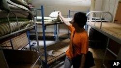 Nhà hoạt động nhân quyền Liu Dejun nhìn qua một căn phòng trong một 'nhà tù đen' ở Bắc Kinh.