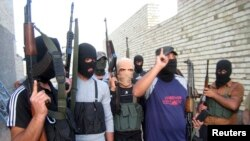 FILE - Masked Sunni gunmen pose during a patrol outside Fallujah, Iraq, April 28, 2014.