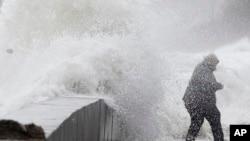 Seorang perempuan terjebak di tengah ombak karena air pasang tinggi terus melanda Wintrhrop, Massachussets, 3 Maret 2018, sehari setelah badai dengan angin, hujan dan salju melanda PesisirAtlantik.