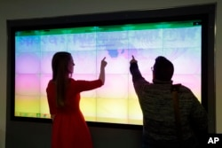 Connecticut College digital scholarship librarian Lyndsay Bratton, left, and assistant professor in Gender and Women's studies Ariella Rotramel, right, use the visualization wall at the Charles E. Shain Library in New London, May 3, 2016.
