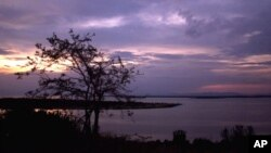 FILE - The sun sets over Lake George near Uganda's Queen Elizabeth National Park in western Uganda.