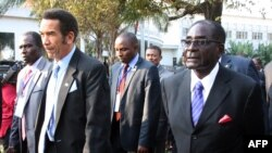 Botswana President Ian Khama (L) walks alongside Zimbabwe President Robert Mugabe (R) during a lunch break at the SADC summit in Maputo, June 15, 2013.