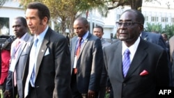 FILE: Botswana President Ian Khama (L) walks alongside Zimbabwe President Robert Mugabe (R) during a lunch break at the SADC summit in Maputo on June 15, 2013. AFP PHOTO / FERHAT MOMADE