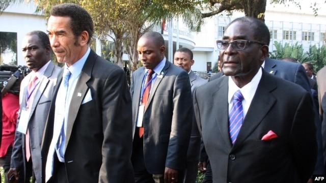 Botswana President Ian Khama (L) walks alongside Zimbabwe President Robert Mugabe (R) during a lunch break at the SADC summit in Maputo, June 15, 2013.