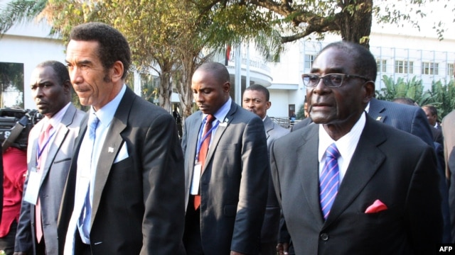 FILE - Botswana President Ian Khama (L) walks alongside Zimbabwe President Robert Mugabe (R) during a lunch break at the SADC summit in Maputo, June 15, 2013.