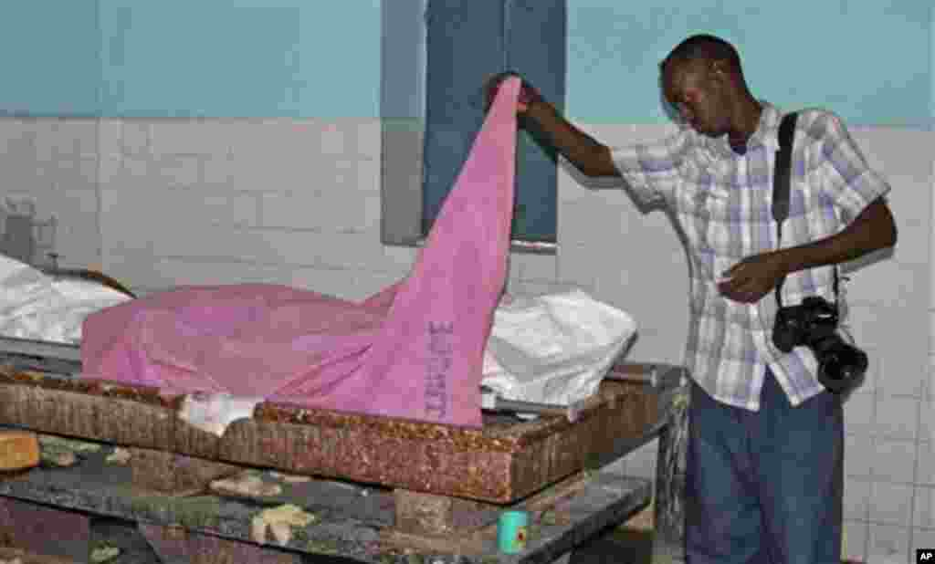 A Somali journalist inspects the body of fellow journalist Abdisalan Sheik Hassan, who was shot dead, at Madina hospital in Mogadishu, Somalia Sunday, Dec, 18, 2011. The director of Somali news station Horn Cable TV says the journalist was shot dead by a