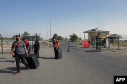 People cross a police checkpoint two kilometers from Friendship Bridge, which separates Uzbekistan and Afghanistan, near Termez, Uzbekistan, Aug. 14, 2021.