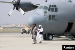 FILE - Taliban members walk in front of a military airplane a day after the U.S. troops' withdrawal from Hamid Karzai International Airport in Kabul, Afghanistan, Aug. 31, 2021.