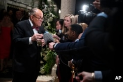 FILE - Rudy Giuliani, an attorney for President Donald Trump, speaks to reporters as he arrives for a New Year's Eve party at Trump's Mar-a-Lago property in Palm Beach, Fla., Dec. 31, 2019.