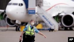 រូបឯកសារ៖ សន្ដិសុខម្នាក់ដើរនៅពីមុនយន្ដហោះ Boeing កាលពីថ្ងៃទី២៩ ខែមេសា ឆ្នាំ២០២០។