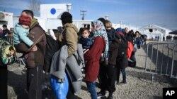 Para migran menunggu diperiksa dokumennya oleh polisi Yunani sebelum diizinkan untuk melalui perbatasan Makedonia, Minggu (21/2).