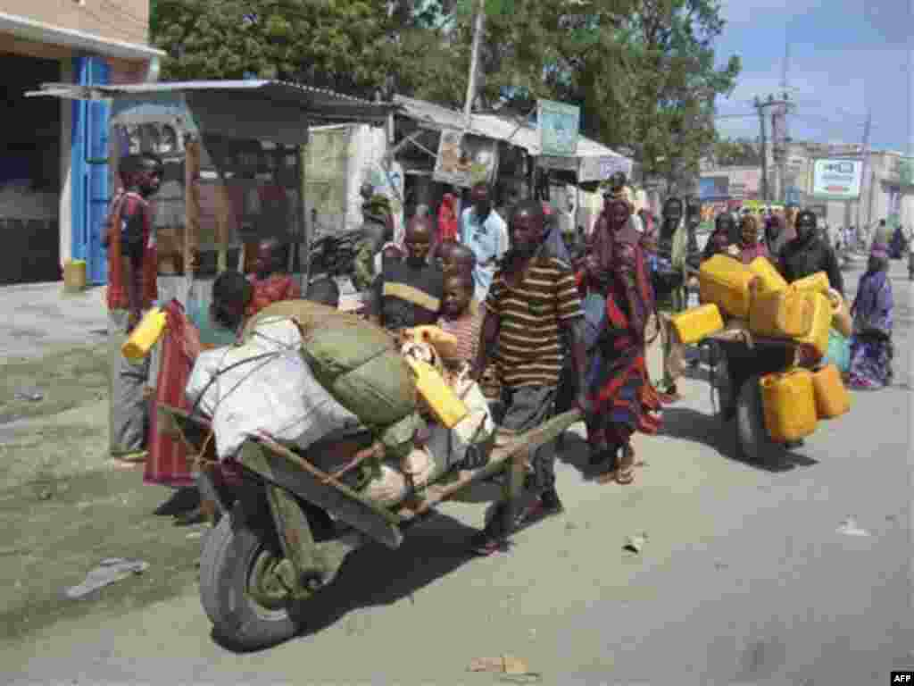 Somalis from southern Somalia carrying their belongings make their way to a new camp for internally displaced people in Mogadishu Somalia, Thursday July, 28, 2011. Heavy fighting erupted Thursday in Somalia's capital as African Union peacekeepers launched