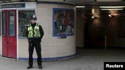 Afisa polisi akifanya doria nje ya kituo cha treni ya chini ya ardhi cha Leystonstone mashariki mwa London, Uingereza.