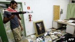 Ливийский повстанец в разгромленном офисе одного из приближенных Каддафи