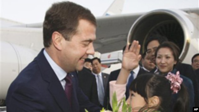 A Chinese girl greets Russia President Dmitry Medvedev, left,  upon his arrival at the Beijing Capital International Airport Sunday, Sept. 26, 2010.