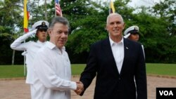 Vice President Mike Pence is welcomed by Colombia's President Juan Manuel Santos, left, in Cartagena, Colombia, Sunday, Aug. 13, 2017.