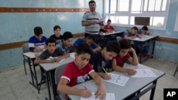 In this Sunday, May 26, 2019 photo, a teacher supervises while Palestinian school children attend a final exam during the last day of the school year, at the UNRWA, Hebron Boys School, in the West Bank city of Hebron. (AP Photo/Nasser Nasser)