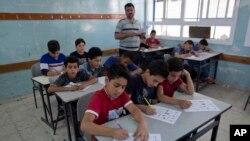 Một thầy giáo đang gác thi kỳ thi cuối năm trong một lớp học ở Palestine