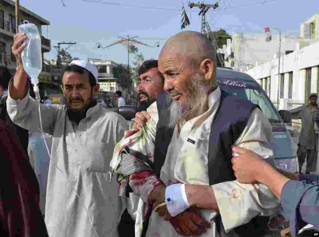 People rush an injured man to a hospital in Quetta, Pakistan, August 9, 2013.