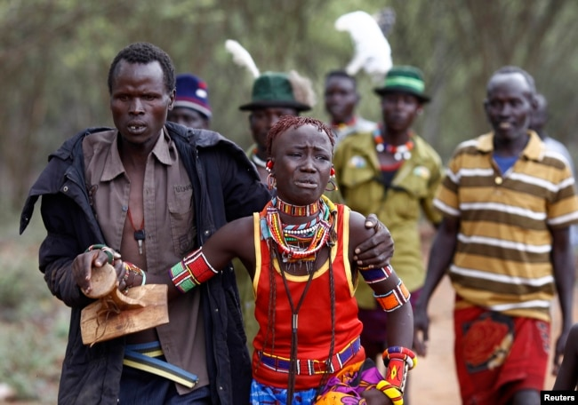 FILE - A man holds onto a girl as he brings her back to her family home after she tried to escape when she realized she is to be married, about 80 km (50 miles) from the town of Marigat in Baringo County, Kenya.