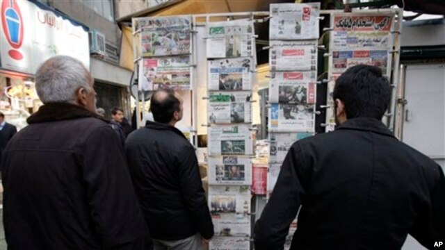 Iranians look at newspapers hanging on a news stand in central Tehran, Feb. 25, 2012.