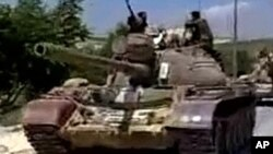 Military tanks drive into the Jabal Al-Zawya area of Idlib on August 1, 2011 in this still image taken from video posted on a social media website. The death toll in Syria's violent crackdown on opposition to President Bashar al-Assad in the city of Hama