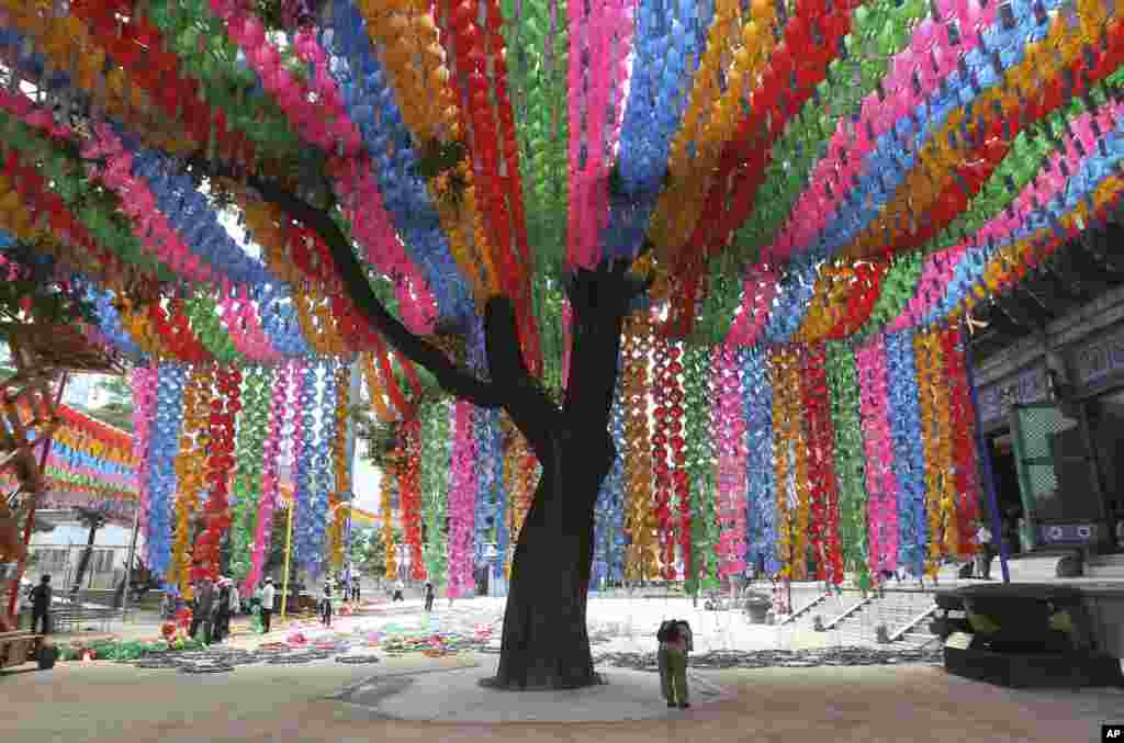 A woman prays as workers prepare to remove lantern decorations after a period of celebrations of Buddha's birthday at the Chogye Temple in Seoul, South Korea.