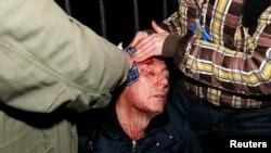 Mantan menteri dalam negeri Ukraina dan pemimpin oposisi Yuriy Lutsenko menerima bantuan medis menyusul bentrokan antara demonstran dan polisi di Kyiv (10/11).
