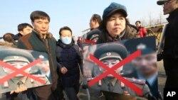 Članovi porodica žrtava sa južnokorejkog broda koji je potonuo nakon napada Severne Koreje drže precrtane portrete čelnika Severne Koreje tokom protesta u Pađu, Južna Koreja, 25. febraura 2018.