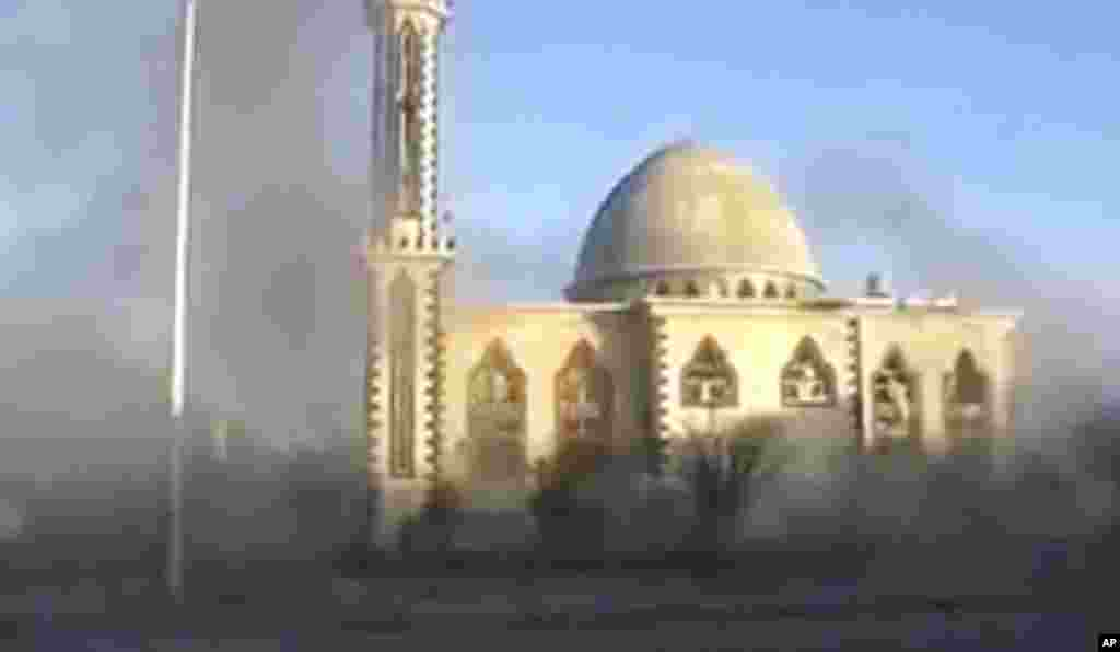 This image from an amateur video purports to show smoke near a mosque in Homs, , February 9, 2012. (AP, via APTN)
