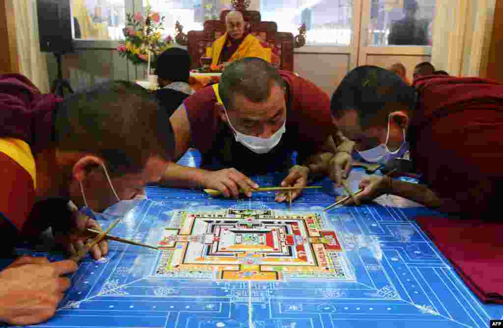 Tibetan Spiritual Leader The Dalai Lama looks on as Tibetan Buddhist monks work on a traditional painting during a special religious prayer at Bodhgaya, India.