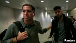 Wartawan AS Glenn Greenwald (kiri) dan pasangannya David Miranda di bandara Rio de Janeiro, 19 Agustus 2013.
