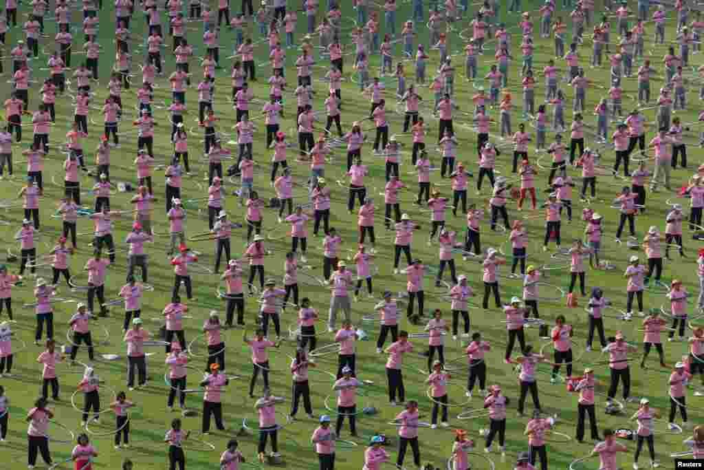 Ribuan warga Thailand berpatisipasi dalam upaya memecahkan rekor Guinness dalam jumlah orang paling banyak yang melakukan hula-hoop bersama-sama di stadion Universitas Thammasat di provinsi Pathum Thani, pinggiran ibukota Bangkok, Thailand.