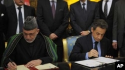 France's President Nicolas Sarkozy (R) and Afghanistan's President Hamid Karzai sign a friendship and cooperation treaty at the Elysee Palace in Paris, January 27, 2012.