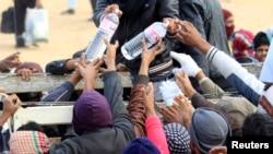Fuyant les violences en Libye, des réfugiés se retrouvent dans un camps en Tunisie où de l'eau est distribuée, à Ras Jdir, le 9 mars 2011.