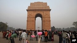 A man sells candy floss in front of the India Gate national monument in New Delhi, India, Dec. 12, 2011.