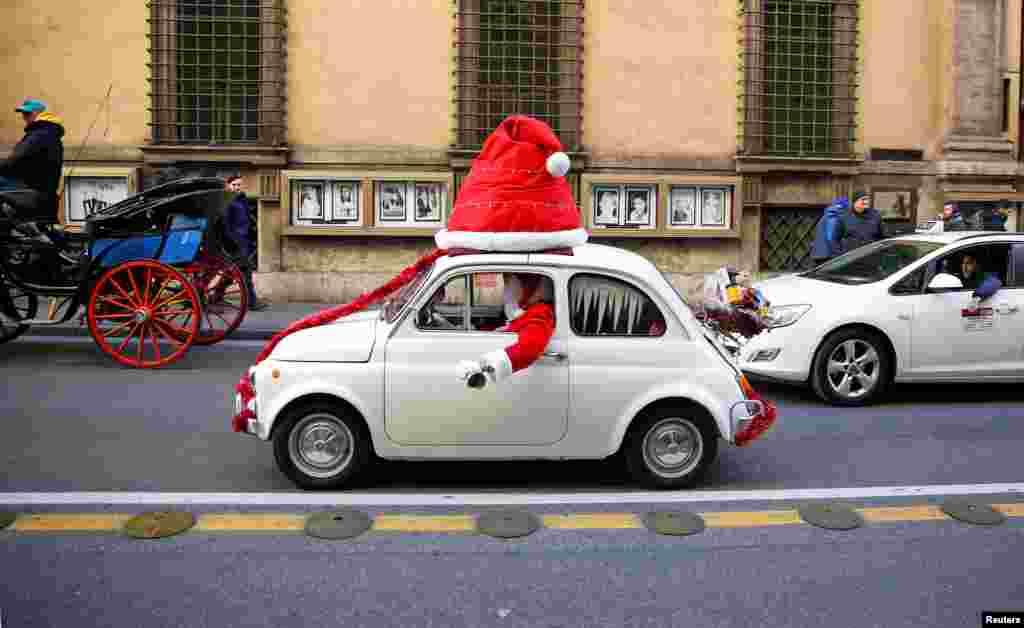បុរសម្នាក់តុបតែងជា Santa Clause វាយកន្តឹងនៅពេលលោកបើករថយន្ត Fiat 500 នៅក្នុងក្រុងរ៉ូម ប្រទេសអ៊ីតាលី កាលពីថ្ងៃទី៩ ខែធ្នូ ឆ្នាំ២០១៧។