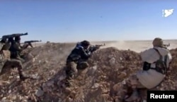 FILE - This photo from a video provided by the Syria Democratic Forces (SDF), shows fighters from the SDF opening fire on an Islamic State group's position, in Raqqa's eastern countryside, Syria, March 6, 2017.