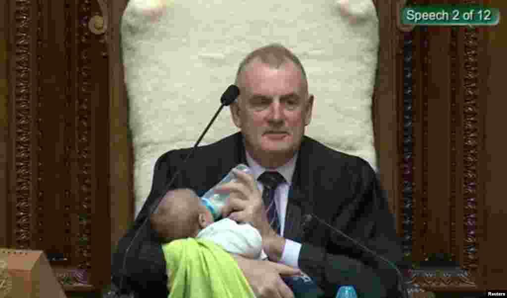 Screenshot from a Parliament broadcast of New Zealand Speaker Trevor Mallard feeding a Member of Parliament's baby during a parliamentary session in Wellington, Aug. 21, 2019. (New Zealand Parliament and Speaker's Office/Handout)
